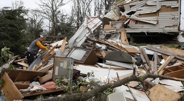 Lee Hoyle, of Chickasaw Nation search and rescue, digs through the debris of a mobile home in the Steelman Estates Mobile Home Park, destroyed by Sunday's tornado, near Shawnee, Okla., Monday, May 20, 2013. The tornado that slammed into Oklahoma on Sunday is now blamed for two deaths. Authorities say two men in their 70s have been found dead in or near a mobile home park outside of Shawnee. (AP Photo Sue Ogrocki)