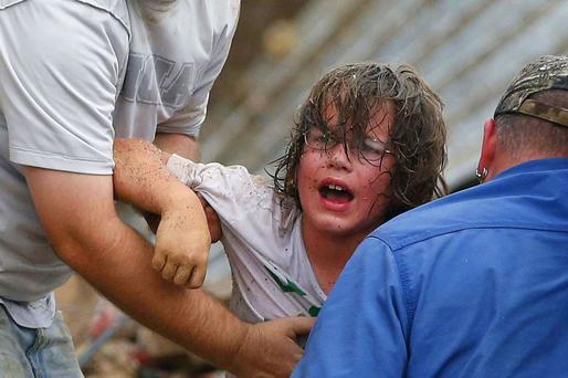 A child calls to his father after being pulled from the rubble of the Tower Plaza Elementary School following a tornado in Moore, Okla., Monday, May 20, 2013