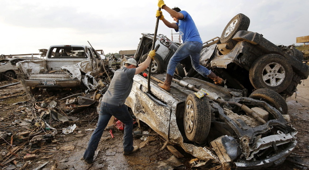 Two men attempt to pry open a door on this car to check for victims in a business parking lot west of I-35 south of 4th Street in Moore, on Monday, May 20, 2013