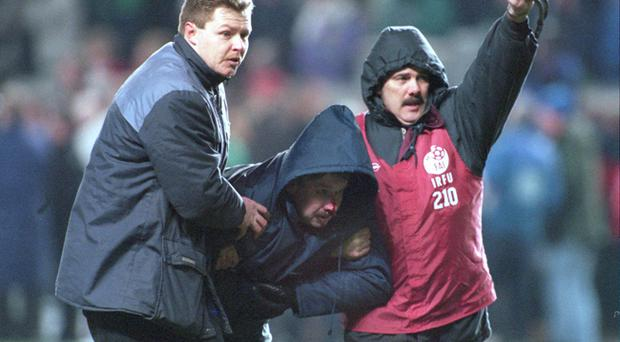 15 FEB 1995: An Irish fan is helped away by stewards after being hit by a missile as England fans riot during the Republic of Ireland v England friendly international at Lansdowne Road in Dublin. The game was abandoned after 27 minutes