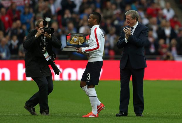 England's captain Ashley Cole is applauded by his manager Roy Hodgson after receiving his 100th cap during the International Friendly match at Wembley Stadium, London.