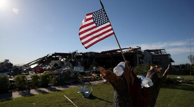 EL RENO, OK - JUNE 01: An American flag sits in a tree stump outside of a restaurant the was damaged by a series of tornadoes that ripped through the area a day earlier on June 1, 2013 in El Reno, Oklahoma. A series of tornadoes ripped through the area on Friday evening killing at least nine people, injuring many others and destroying homes and buildings. (Photo by Justin Sullivan/Getty Images)