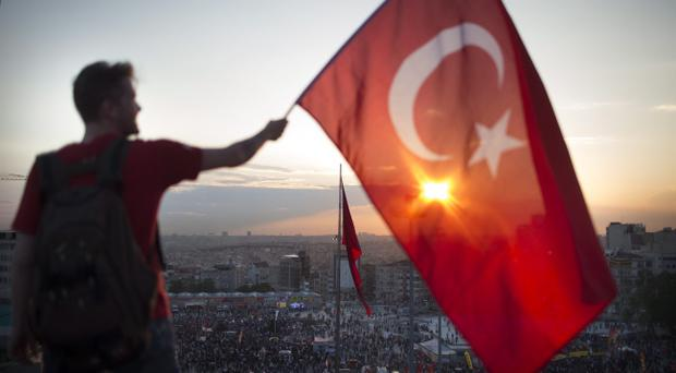 ISTANBUL, TURKEY - JUNE 03: A protestor waves the Turkish flag from a roof top at Taksim square on June 3, 2013 in Istanbul, Turkey. The protests began initially over the fate of Taksim Gezi Park, one of the last significant green spaces in the center of the city. The heavy-handed viewed response of the police, Prime Minister Recep Tayyip Erdogan and his government's increasingly authoritarian agenda has broadened the rage of the clashes. (Photo by Uriel Sinai/Getty Images)v?