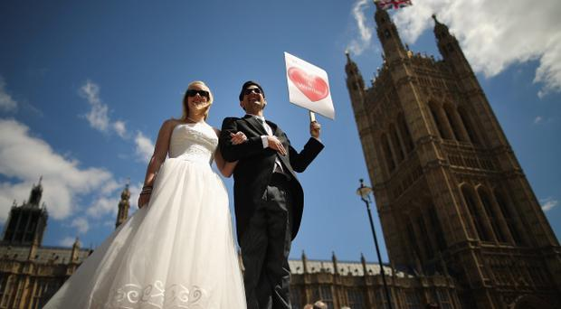Proponents of single sex marriage dressed as a bride and groom, Carrie Hardy, and Martin Etchart of Argentina, stand outside the Houses of Parliament on June 3, 2013 in London, England