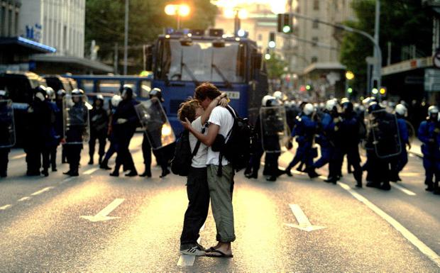 GENEVA - JUNE 2: A couple kiss near a phalanx of German riot police June 2, 2003 in Geneva, Switzerland ahead of that year's G8 summit, the first since the war on Iraq. As the G8 comes to Lough Erne, Fermanagh next week, security is being significantly stepped up at sites around Northern Ireland as protests are expected to take place
