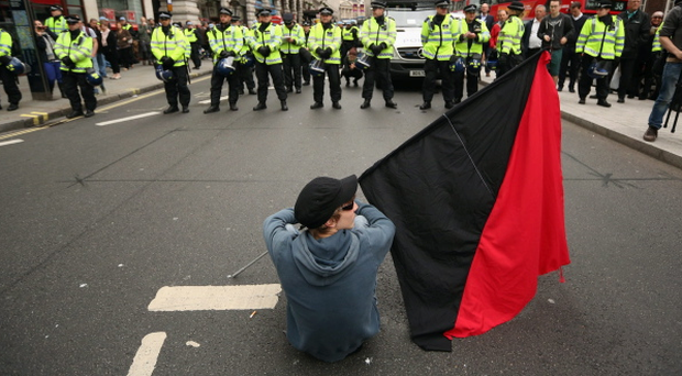 A protester sits on Piccadilly in front of a police line during a demonstration ahead of next week's G8 summit in Northern Ireland on June 11, 2013 in London, England.