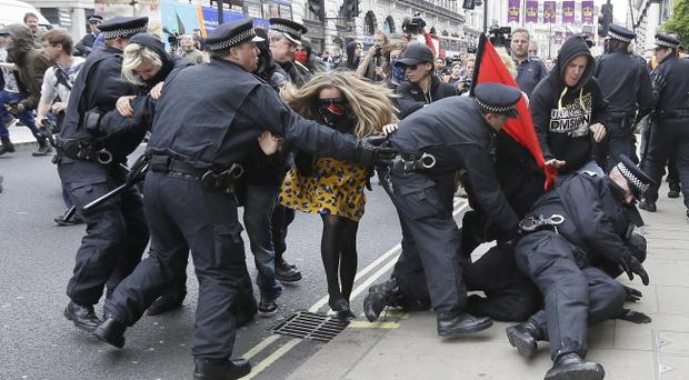 Demonstrators are detained by police during a protest in London, Tuesday, June 11, 2013 .The protestors were demonstrating against the upcoming G8 summit in Northern Ireland on June 17 and 18. (AP Photo/Alastair Grant)