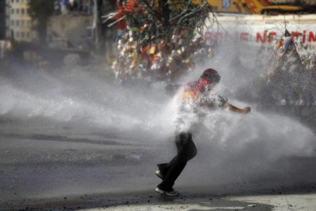 A protester tries to remain standing as police water cannon fires water during clashes in Taksim square in Istanbul, Tuesday, June 11, 2013. Hundreds of police in riot gear forced through barricades in Istanbul's central Taksim Square early Tuesday, pushing many of the protesters who had occupied the square for more than a week into a nearby park. (AP Photo/Kostas Tsironis)