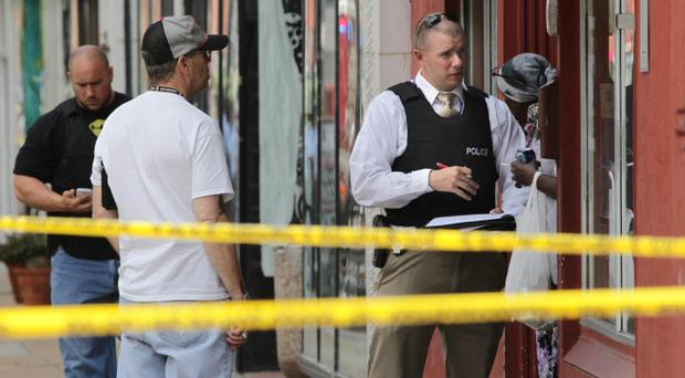 Police at the scene where four people were found dead in a business along Cherokee Street south of downtown St. Louis, on Thursday, June 13, 2013. The St. Louis Police Department posted on its official Twitter account that two women and two men are dead. (AP Photo/St. Louis Post-Dispatch, Robert Cohen)