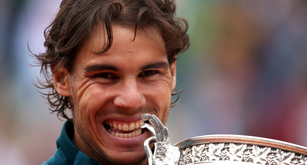 PARIS, FRANCE - JUNE 09: Rafael Nadal of Spain bites the Coupe des Mousquetaires trophy as he celebrates after the men's singles final against David Ferrer of Spain during day fifteen of the French Open at Roland Garros on June 9, 2013 in Paris, France. (Photo by Clive Brunskill/Getty Images)