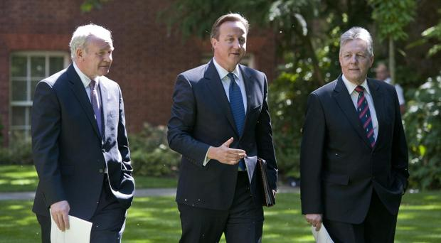 Prime Minister David Cameron (centre) walks with Northern Ireland's Deputy First Minister Martin McGuinness (left) and Northern Ireland's First Minister Peter Robinson (right) for a press conference in the garden of 10 Downing Street in central London.