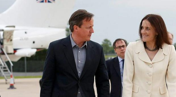 Prime Minister David Cameron walks with Northern Ireland Secretary Theresa Villiers (second right) and Wing Commander Faye Wiseman (left) after arriving at Belfast International Airport, Northern Ireland, ahead of the G8 Summit.