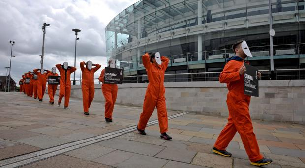 Protesters from Amnesty International dressed in orange jump suits and masks, hold placards requesting that President of the United States, Barack Obama, closes Guantanamo, as they congregate outside the Waterfront, Belfast, ahead of the G8 summit. PRESS ASSOCIATION Photo. Picture date: Sunday June 16, 2013. See PA story POLITICS G8. Photo credit should read: Ben Birchall/PA Wire