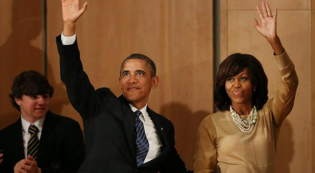 BELFAST, NORTHERN IRELAND - JUNE 17: President Obama and First Lady Michelle wave to the audience in the Waterfront Hall on June 17, 2013 in Belfast, Northern Ireland. Later The President will join other leaders at the G8 Summit in Fermanagh. (Photo by Peter Macdiarmid/Getty Images)