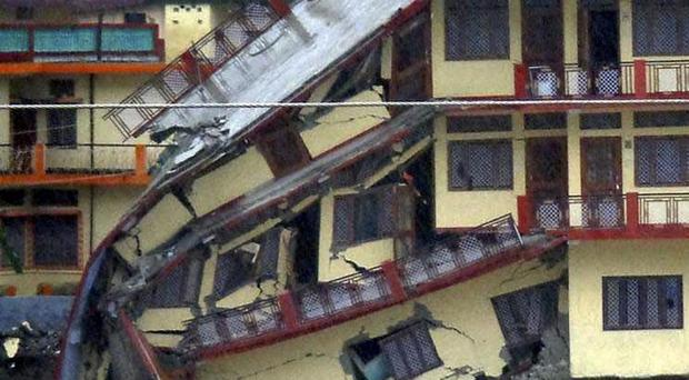 In this Sunday, June 16, 2013 photo, a three-story building is destroyed by floodwaters, in Uttarkash, in northern Indian state of Uttarakhund. Government officials say at least 23 people have died and about 50 are missing after three days of torrential rain washed away buildings and roads in northern India. (AP Photo)