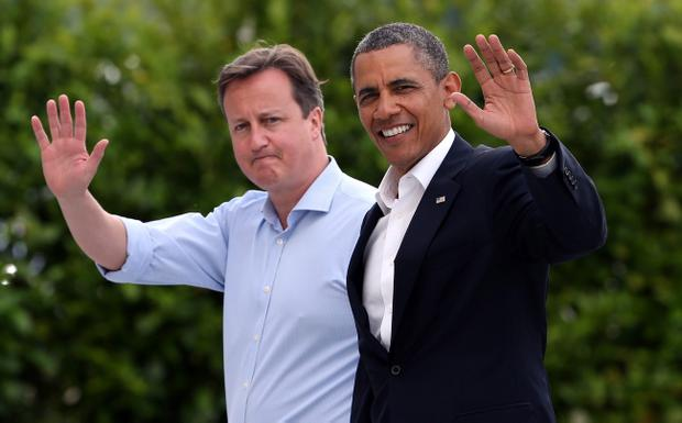 Britain's Prime Minister David Cameron and US President Barack Obama wave as they arrive at the G8 venue of Lough Erne on June 17, 2013 in Enniskillen, Northern Ireland. The two day G8 summit, hosted by UK Prime Minister David Cameron, is being held in Northern Ireland for the first time. Leaders from the G8 nations have gathered to discuss numerous topics with the situation in Syria expected to dominate the talks. (Photo by Matt Cardy/Getty Images)