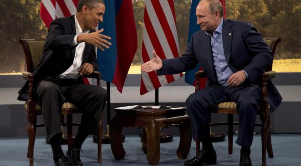 President Barack Obama and Russian President Vladimir Putin reach to shake hands in Enniskillen, Northern Ireland, Monday, June 17, 2013. Obama and Putin discussed the ongoing conflict in Syria during their bilateral meeting. (AP Photo/Evan Vucci)