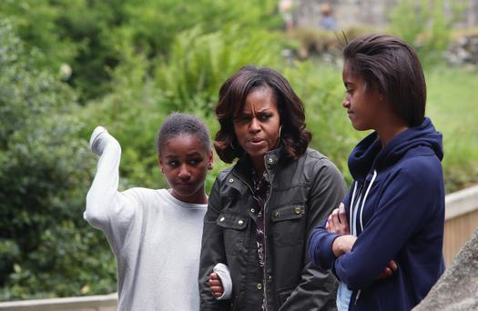 US First Lady Michelle Obama and her two daughters Malia Ann (right) and Sasha fight off an unwelcome attack of midges whilst listening to Head Tour Guide George McClafferty explain about the historically important monastic site of Glendalough, Co Wicklow
