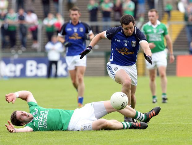 Cavan's Alan Clarke powers through against Eoin Donnelly of Fermanagh