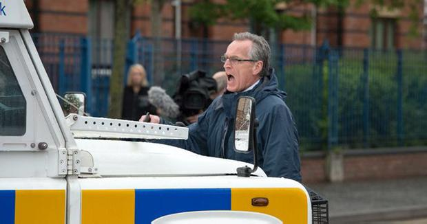 Sinn Fein Gerry Kelly being carried by a police jeep