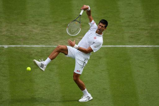 LONDON, ENGLAND - JUNE 25: Novak Djokovic of Serbia stretches to smash the ball during his Gentlemen's Singles first round match against Florian Mayer of Germany on day two of the Wimbledon Lawn Tennis Championships at the All England Lawn Tennis and Croquet Club on June 25, 2013 in London, England. (Photo by Julian Finney/Getty Images)