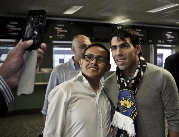 Carlos Tevez, right, wearing a Juventus scarf poses with a fan as he arrives at Malpensa airport, in Varese, Italy, Wednesday, June 26, 2013. Carlos Tevez's turbulent Manchester City career is coming to an end after the Premier League club agreed to sell the Argentina striker to Juventus. (AP Photo/Davide Spada, LaPresse)