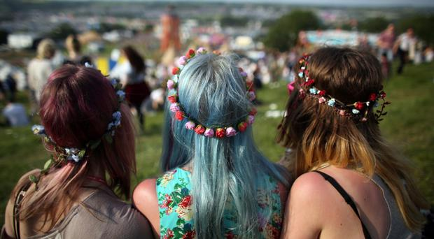GLASTONBURY, ENGLAND - JUNE 26: Three festival goers sit and look at the view at the Glastonbury Festival of Contemporary Performing Arts site