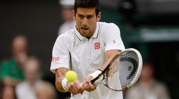 LONDON, ENGLAND - JUNE 27: Novak Djokovic of Serbia plays a backhand during his Gentlemen's Singles second round match against Bobby Reynolds of the United States of America on day four of the Wimbledon Lawn Tennis Championships at the All England Lawn Tennis and Croquet Club on June 27, 2013 in London, England. (Photo by Dennis Grombkowski/Getty Images)