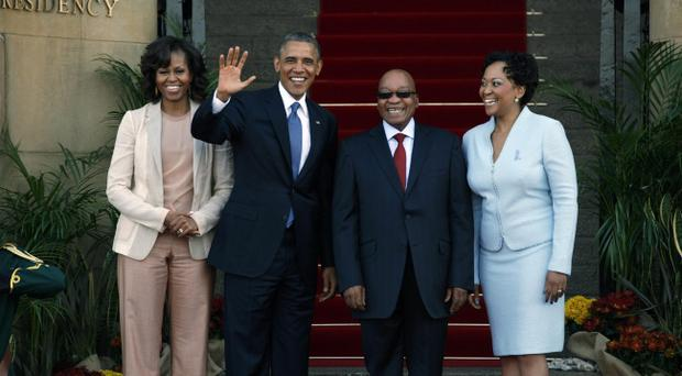 U.S. President Barack Obama flanked by First Lady Michelle Obama, left, waves with South African President Jacob Zuma, second right, and his wife Tobeka Madiba Zuma, right, on the steps of Union Building in Pretoria, South Africa, Saturday June 29, 2013. (AP Photo/Jerome Delay)
