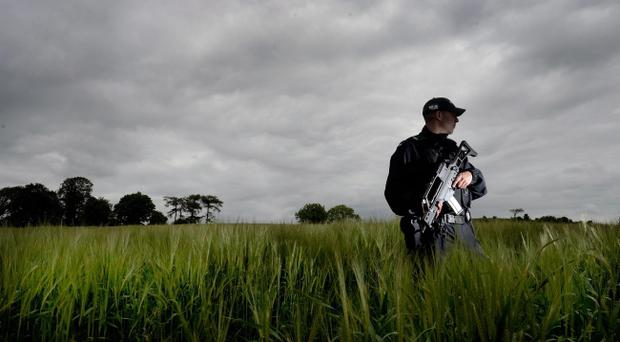 An armed PSNI officer stands guard in the fields overlooking the Lough Erne resort on Sunday 16 June just hours before the beginning of the G8 summit at the Lough Erne resort, Enniskillen. Picture Charles McQuillan/Pacemaker.