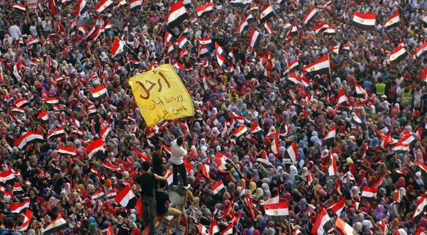 Opponents of Egypt's Islamist President Mohammed Morsi protest as they shout slogans and wave national flags in Tahrir Square in Cairo, Egypt, Tuesday, July 2, 2013
