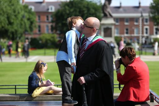Five-year-old Joshua McColgan gives his Dad Jonathan a kiss before he graduates in Collaborative Leadership for Schools at Queen's University, Belfast, Northern Ireland, 4rd July 2013. Photo/Paul McErlane
