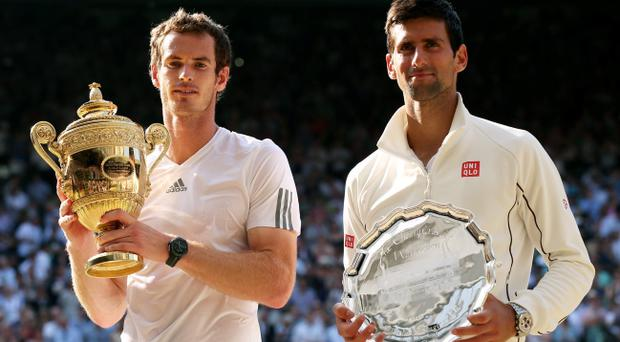 LONDON, ENGLAND - JULY 07: Andy Murray of Great Britain poses with the Gentlemen's Singles Trophy next to Novak Djokovic of Serbia following his victory in the Gentlemen's Singles Final match on day thirteen of the Wimbledon Lawn Tennis Championships at the All England Lawn Tennis and Croquet Club on July 7, 2013 in London, England. (Photo by Clive Brunskill/Getty Images)