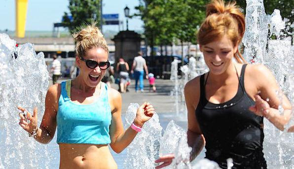Pacemaker Press 8/7/2012 Josephine McAllister and Kirsty McClean cool down in the water fountain in Belfast City Centre , as hot spells hit across Northern Ireland Pic Colm Lenaghan/Pacemaker