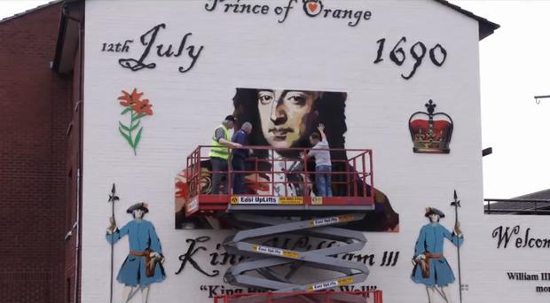 The local community and artist Ross Wilson painted over the paramilitary gunman and replaced it with 'A Portrait of a King', a mural of King William III.