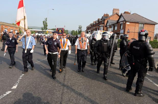 PSNI in riot gear, escort a Orange feeder parade past the Ardoyne shops, in Belfast as tensions were high over the Orange Order parades on the 12th July. PRESS ASSOCIATION Photo. Picture date: Friday July 12, 2013. A major security operation will be in place for traditional Twelfth of July commemorations in Belfast today with Orangemen set to protest over the banning of a controversial parade. See PA story ULSTER Parades. Photo credit should read: Paul Faith/PA Wire