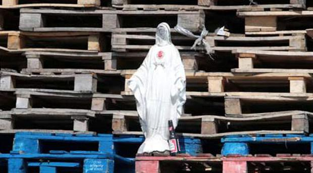 A statue of our the Virgin Mary placed on a loyalist bonfire at Lanark Way PACEMAKER