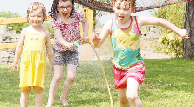 Five-year-old Erin Cherry (centre) soaks her sister Corah(3) and their friend Evan Coates (5) with the watering hose in their back garden in Saintfield, Co. Down