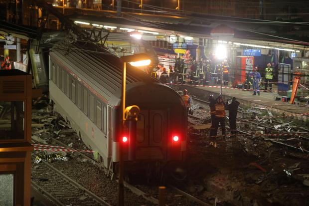 The scene where a train derailed, at the station, in Bretigny sur Orge, south of Paris, Friday, July 12, 2013. A packed passenger train skidded off its rails after leaving Paris on Friday, leaving seven people believed dead and dozens injured as train cars slammed into each other and overturned, authorities said. (AP Photo/Michel Euler)