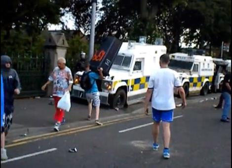 As the PSNI officers stand behind riot shields, loyalist thugs carry out a sustained attack at arm's length.