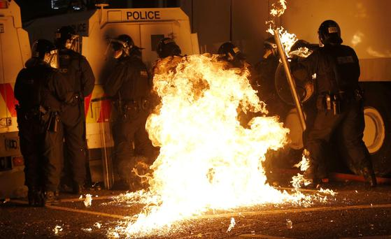 A petrol bomb hits riot police after it was thrown by loyalist rioters in the Woodvale area of north Belfast