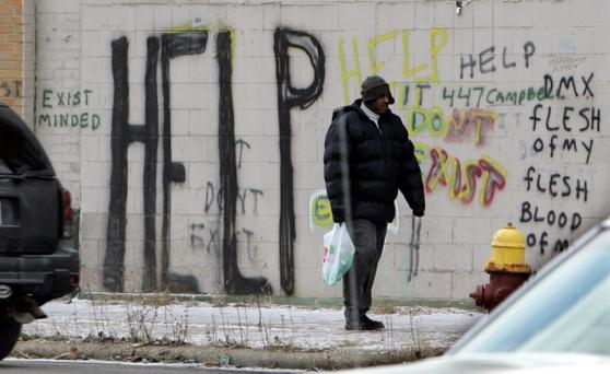 A pedestrian walks by graffiti in downtown Detroit