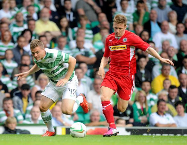 Celtic's James Forrest and Cliftonville's Stephen Garrett tussle during the UEFA Champions League, second round, second leg match at Celtic Park, Glasgow