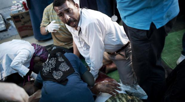 Doctors treat a supporter of Egypt's ousted President Mohammed Morsi injured during clashes with security forces at Nasr City, where pro-Morsi protesters have held a weeks-long sit-in