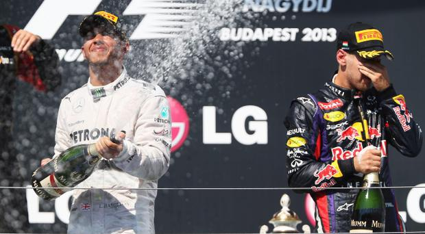 BUDAPEST, HUNGARY - JULY 28: Race winner Lewis Hamilton (L) of Great Britain and Mercedes GP celebrates on the podium with third placed Sebastian Vettel (R) of Germany and Infiniti Red Bull Racing following the Hungarian Formula One Grand Prix at Hungaroring on July 28, 2013 in Budapest, Hungary. (Photo by Mark Thompson/Getty Images)