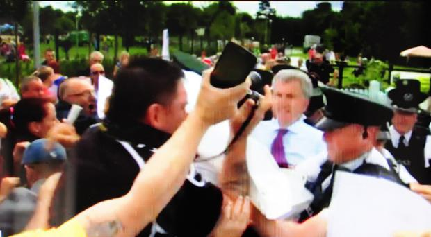 Lord Mayor of Belfast, Máirtín Ó Muilleoir, was escorted from the ceremony at Woodvale by police after protesters gathered at the community garden