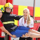 Ultimate Firefighter competition at the Titanic Slipway in the Titanic Quarter of Belfast City Centre. Volunteers and sponsor Coke employees Zoe Cunningham(left) Ashley McIntyre(right) with firefighter and Crew Commander Blue Central Danny Ard. Photo-Jonathan Porter/Presseye.