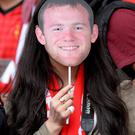 A fan holds a Wayne Rooney mask before Rio Ferdinand's Testimonial match at Old Trafford, Manchester