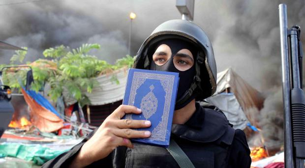 A member of the Egyptian security forces holds up a copy of the Quran as clear they clear the smaller of the two sit-ins by supporters of ousted Islamist President Mohammed Morsi, near the Cairo University campus in Giza, Cairo, Egypt, Wednesday, Aug. 14, 2013. Egyptian security forces, backed by armored cars and bulldozers, moved on Wednesday to clear two sit-in camps by supporters of the country's ousted President Mohammed Morsi, showering protesters with tear gas as the sound of gunfire rang out at both sites. (AP Photo/Imad Abdul Rahman)