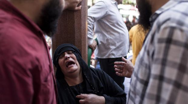An Egyptian woman cries after identifying the body of a family member, a supporter of deposed Egyptian President Mohammed Morsi killed during a violent crackdown by Egyptian Security Forces on pro-Morsi sit-in demonstrations the day before, at the al-Iman Mosque in Nasr City on August 15, 2013 in Cairo, Egypt